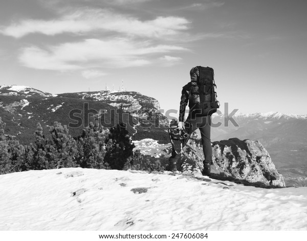 Tourist with big backpack and snowshoes standing on rocky view point and watching into misty rocky mountains. National park Alps park in Italy. Sunny winter morning.
