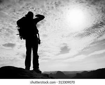 Tourist with big backpack stand on rocky view point and watching into deep misty valley bellow. Black and white photo. ,