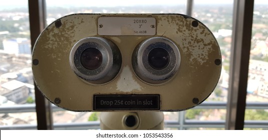 Tourist Binoculars over high tower. It look funny because it look like man or robot face.