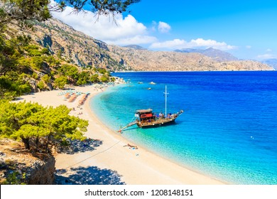 Tourist boat anchoring at beautiful Apella beach on Karpathos island, Greece