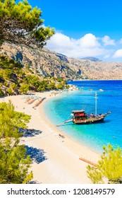 Tourist boat anchoring at beautiful Apella beach on Karpathos island, Greece