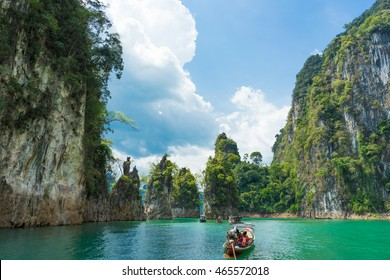 Tourist boat exploring epic limestone cliffs in huge lake in Khao Sok National Park, Chiew lan lake, Thailand.
