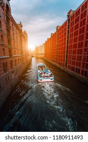 Tourist boat in famous Speicherstadt warehouse district with low clouds in Hamburg, Germany