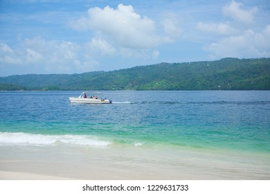 tourist boat floating in the waters of Samana Bay near the island Cayo Levantado. Boat is white. sky and water are blue. Cayo Levantado, also known as Bacardi Island, is an islet in Samana Bay
