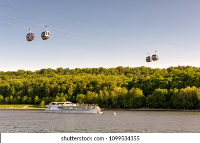 Tourist boat floats along the Moskva River, Moscow, Russia. Scenic view of the cable car between Sparrow Hills and Luzhniki Stadium in Moscow. Cableway cabins hang in the sky in Moscow Luzhniki park.