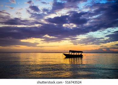 A tourist boat moored just off the beach at sunrise in the Dominican Republic.