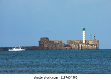Tourist boat passing along the pier with the lighthouse of Boulogn-sur-Mer