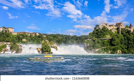 Tourist boat with people floating to the waterfall the Rhine Falls. It is one of the main tourist attractions, Schaffhausen, Switzerland.