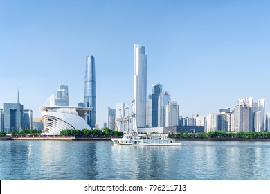 Tourist boat sailing along the Pearl River in Guangzhou, China. Beautiful view of skyscrapers and other modern buildings at the Zhujiang New Town. Amazing Guangzhou skyline. Sunny summer cityscape.
