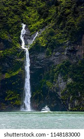 Tourist boat steers close to waterfalls plunging from mountain face covered with trees.