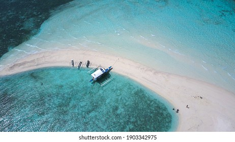 A tourist boat and three smaller fishing bancas anchored right by the shore of a crescent shaped sandbar. Shot in Bohol, Philippines. Tourism and adventure concept. - Shutterstock ID 1903342975