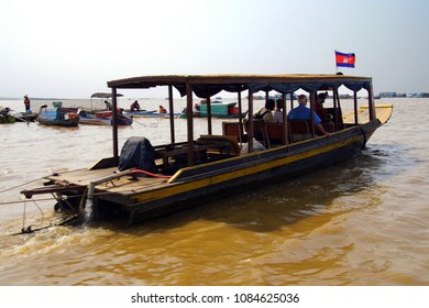 Tourist boat travels along the waterway of Kompong Kleang floating fishing village,  Cambodia