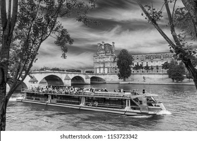 Tourist boat travels on the Seine River in Paris in black and white