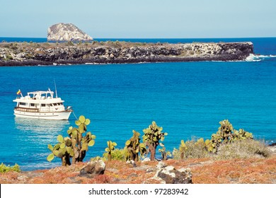 Tourist boat visits South Plaza with red sesuvium and prickly pear cactus vegetation in foreground, Galapagos Islands, Ecuador