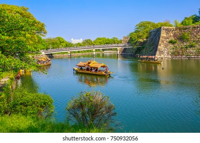 Tourist boats along the moat and the wall of Osaka Castle while crossing the popular Gokurakubashi Bridge or Gokuraku Bridge leading to Osaka Castle Park. Osaka city, Japan.