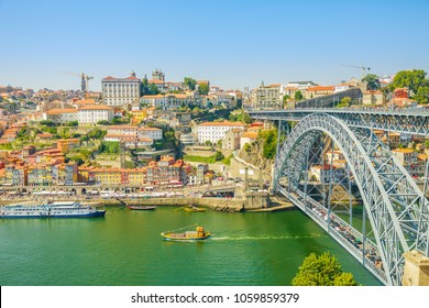 Tourist boats cruising under Douro River in Porto. Aerial view of Dom Luis I Bridge, Ribeira Waterfront and Rabelo boats from Vila Nova de Gaia, Porto, Portugal. Oporto urban cityscape in blue sky.