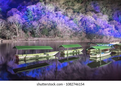 Tourist boats and illuminated mountain during Arashiyama Hanatouro festival, Kyoto, Japan.