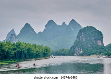 Tourist boats on Li river with dramatic karst mountain landscape in the background. Yangshuo, China