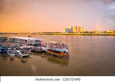 Tourist boats on the Mekong river at the pier of Phnom Penh city, capital of Cambodia, Asia, with beautiful light and rainbow in the sky rainbow
