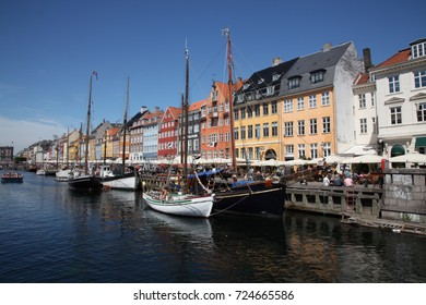 Tourist boats sail in old town Nyhavn,  a 17th century waterfront pier harbor, colored houses, boats, canal and entertainment district. Copenhagen, Denmark, July 5th, 2015