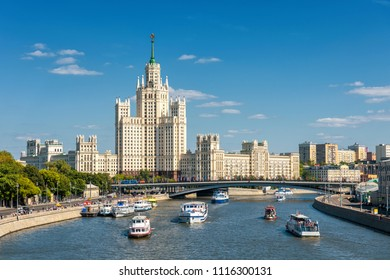 Tourist boats sail on the Moskva River in summer, Moscow, Russia. Panoramic view of Moscow centre. Scenic panorama of Moscow with old Soviet Stalin skyscraper on sunny day. Water trip across Moscow.