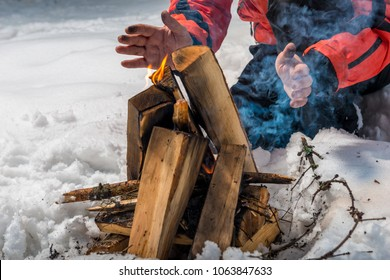 the tourist builds a fire in the winter forest and heats his hands