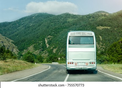 Tourist bus on the road among the green mountains. Back view