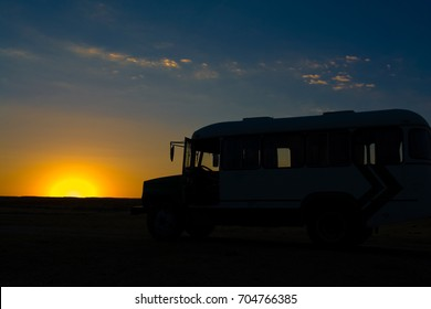 tourist bus in the steppes of Kazakhstan against the sunset -