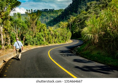 A tourist with camera walking along a winding rural road near San Jernonimo, Costa Rica