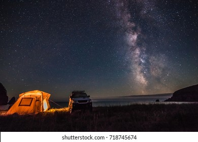 Tourist camping at sea coast at night with milky way. Some noise from hugh iso exists