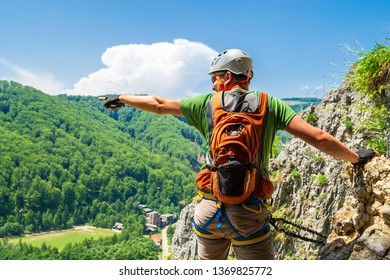 Tourist climber pointing his hand into distance on a via ferrata route in Baia de Fier, Gorj county, Romania. Male climber equipped with helmet, climbing harness, klettersteig set, and cutout gloves.