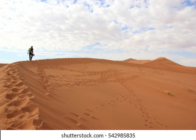 A tourist is climbing a dune in the Sossusvlei desert, Namibia