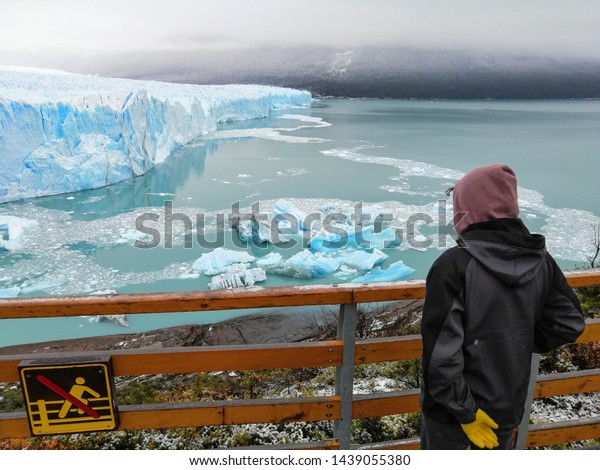 """Tourist in coat and hood, with yellow gloves, standing at the handrail contemplating the glacier """"Perito Moreno"""" and the lake; Warning sign """"Don't cross handrail"""""""