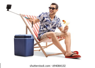 Tourist with a cocktail sitting in a deck chair and taking a selfie with a stick isolated on white background