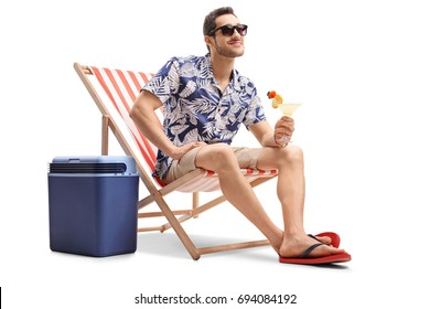 Tourist with a cocktail sitting in a deck chair next to a cooling box and looking away isolated on white background