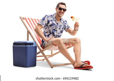 Tourist with a cocktail sitting in a deck chair next to a cooling box and looking at the camera isolated on white background