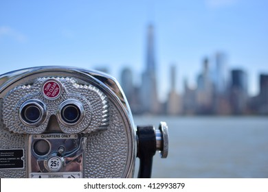Tourist coin operated binoculars at Liberty Island in front of Manhattan Skyline, New York City, USA