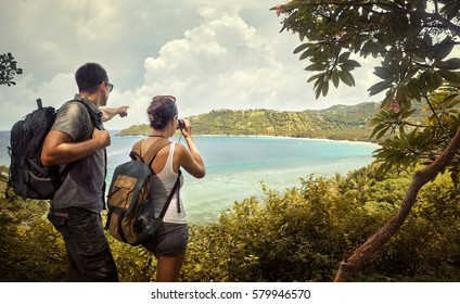 Tourist couple  with backpacks enjoying views coast island Lombok. Indonesia.Traveling along mountains and coast, freedom and active lifestyle concept.