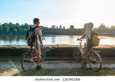 Tourist couple cycling in Angkor temple, Cambodia. Angkor Wat main facade reflected on water pond. Eco friendly tourism traveling.