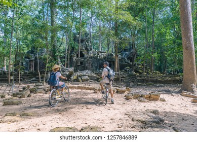 Tourist couple cycling around Angkor temple, Cambodia. Ta Nei small building ruins in the jungle. Eco friendly tourism traveling.