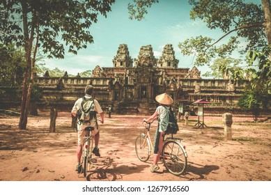 Tourist couple cycling around Angkor temple, Cambodia. Ta Keo building ruins in the jungle. Eco friendly tourism traveling, toned image.