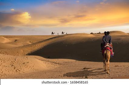 Tourist couple enjoy a camel safari at sunset at the Thar desert Jaisalmer Rajasthan, India
