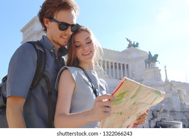 Tourist couple enjoying city sightseeing. Young man and woman looking into the map and smiling in a beautiful sunny day in Rome, Italy.