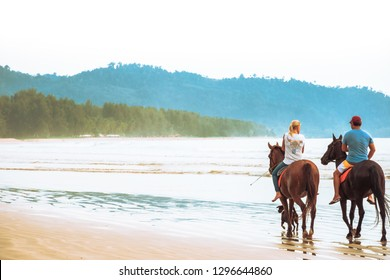 Tourist couple is enjoying riding horses on the beach with beautiful view in Thailand. People having fun on summer vacation in Thailand. Horse riding for rent.