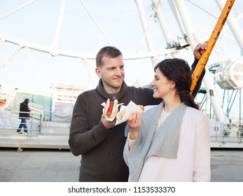 Tourist couple in fun fair enjoying day out activities, smiling together eating hot dog fast food outdoors. Man and woman holding junk food in amusement park, recreation leisure lifestyle.