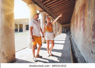 Tourist couple is looking to frescoes on the wall in Pompeii ancient city Italy