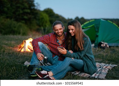 Tourist Couple In Love With Phone Near Camping In Nature. Portrait Of Young Lovely People Looking At Mobile Phone While Having Romantic Getaways. Couples Vacations. High Resolution.