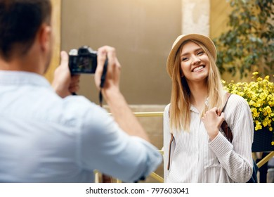 Tourist Couple. Man With Camera Taking Photos Of Woman In Street. Smiling Young Couple In Love In Stylish Clothes Traveling And Making Photos Outdoors. People Travel On Weekend. High Resolution.