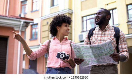 Tourist couple with map and photo camera, choosing direction, travelling