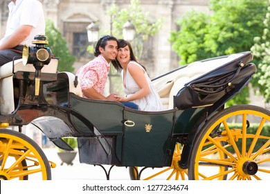 Tourist couple on city break vacation riding in horse drawn carriage